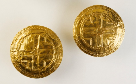 Pair of gold discs, Tedavnet, Co. Monaghan. Early Bronze Age, 2200–2000 bc. Discovered in the roots of an old tree, this pair of discs is the largest and most sophisticated of the Early Bronze Age discs known from Ireland. A complex arrangement of raised lines, rows of dots and zig-zags has produced a central cross surrounded by concentric patterns similar to other discs but much more elaborate in composition and, technically, far superior. The combination of the techniques of repoussé, punching and polishing, together with the slight doming of the surfaces, highlights and gives a depth and texture to the discs not seen on other pieces. 1872:34, 35. D. 11.3 and 11.5 cm; Wt. 22.5 and 22.8 g.Armstrong 1920, 84; Cahill 1983, no. 6.